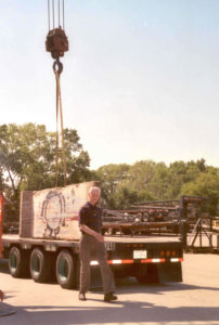 Tom Drysdale with section of Berlin Wall being unloaded from truck trailer bed.