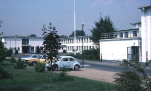 Photo of exterior of Frankfrut High School with cars